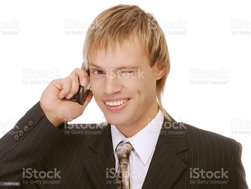 Young businessman winks and speaks by phone royalty-free stock photo