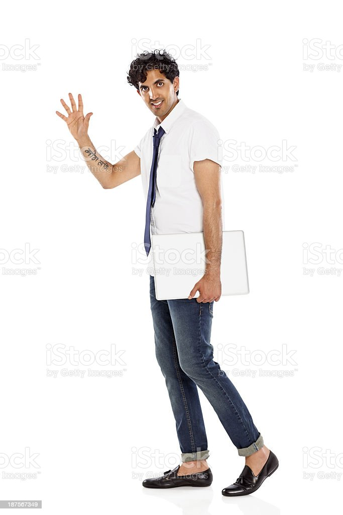 Young businessman with a laptop waving at camera royalty-free stock photo