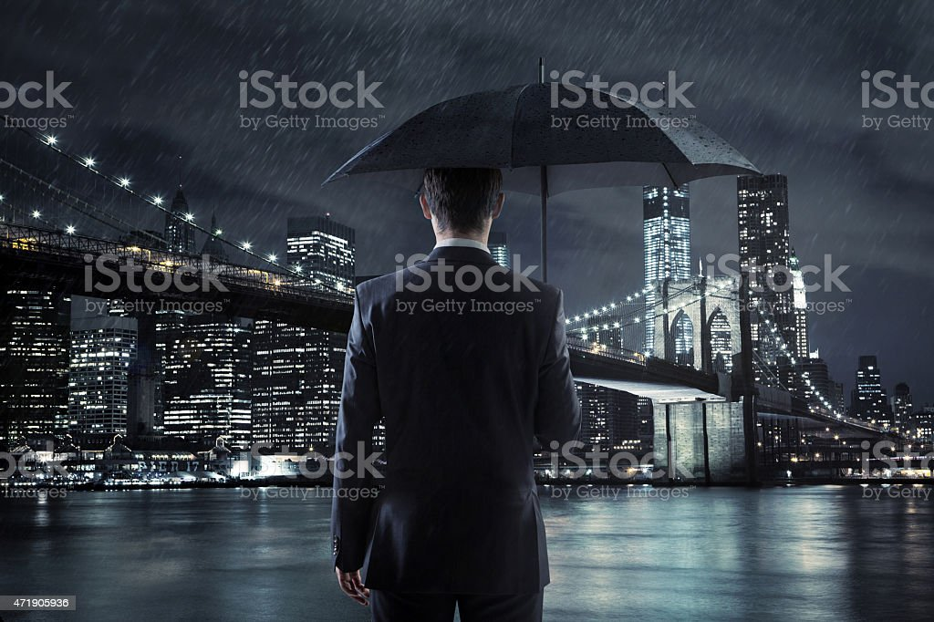 Young businessman with an umbrella over the night city backgroun stock photo