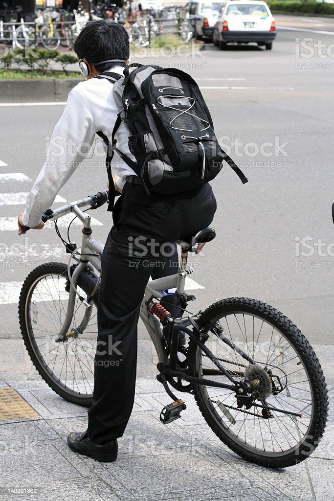 Young businessman with backpack on a bicycle royalty-free stock photo