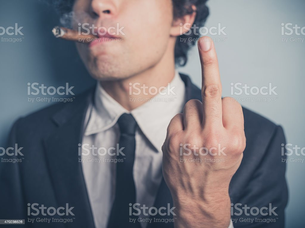 Young businessman with cigar showing rude gesture stock photo