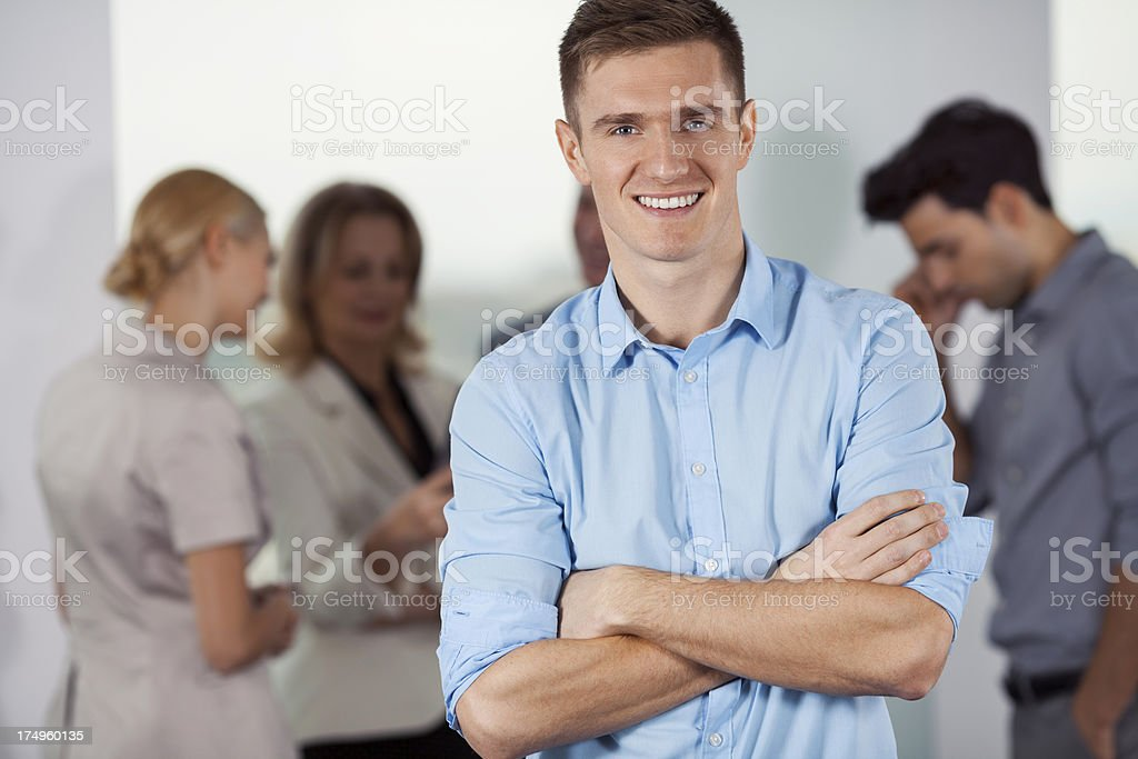 Young businessman with colleagues in backgroung royalty-free stock photo