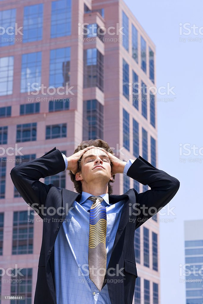 young businessman with hands in hair, stretching towards the sun royalty-free stock photo