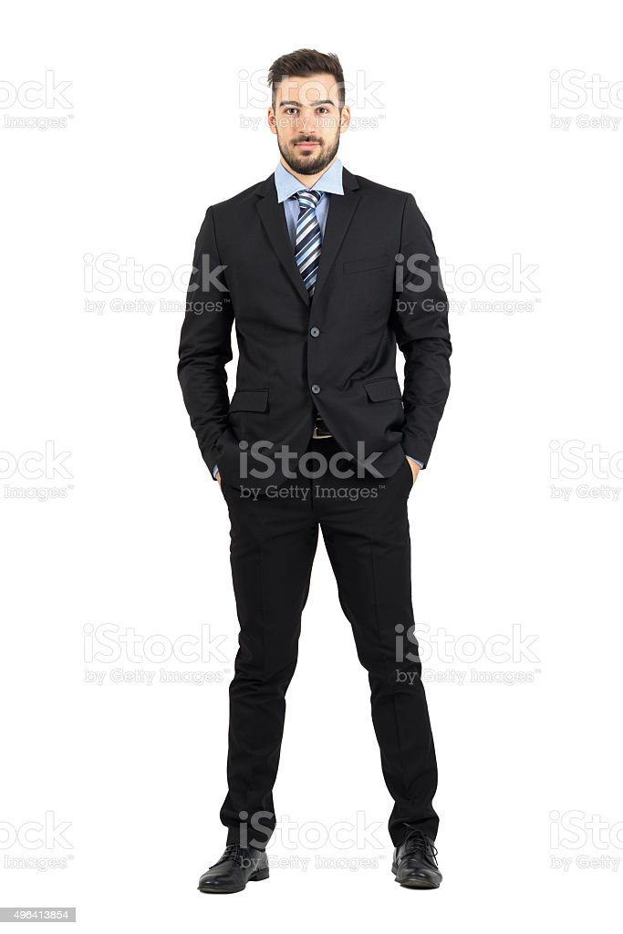 Young businessman with hands in pockets looking at camera stock photo