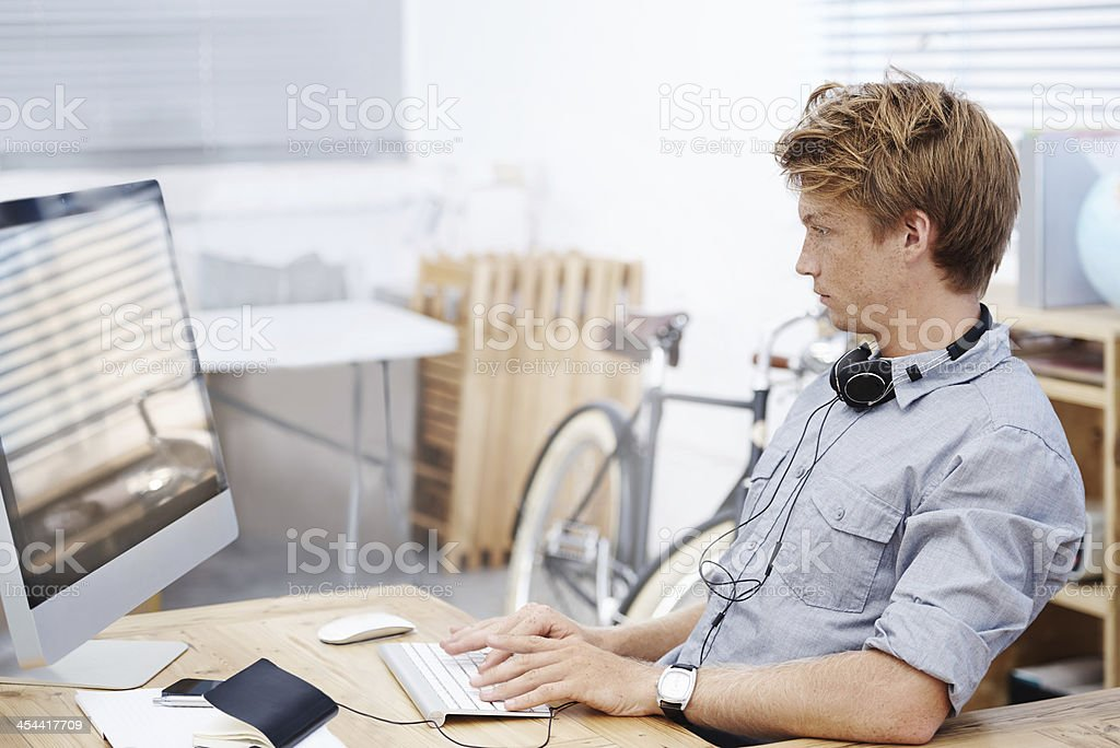Young businessman with headphones working on office desktop stock photo