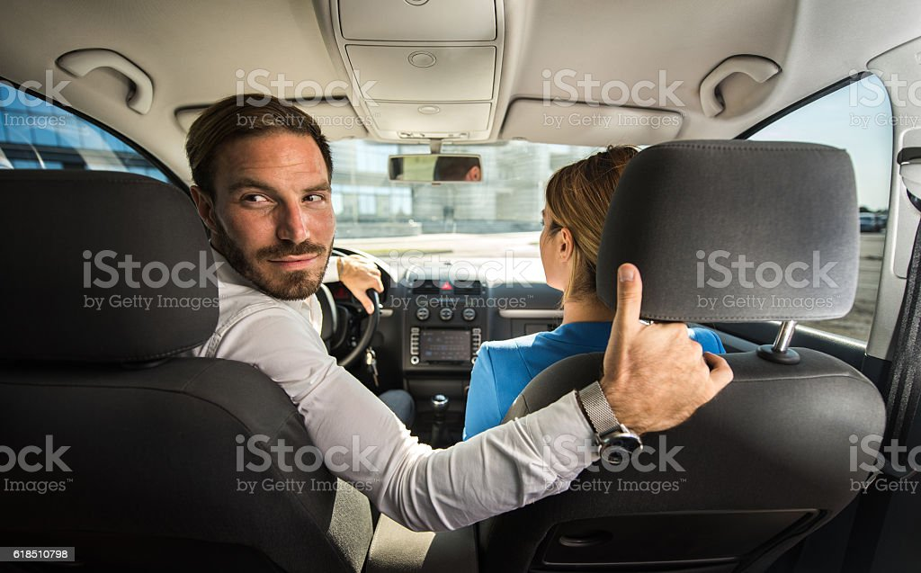 Young businessman with his colleague driving reversing. stock photo
