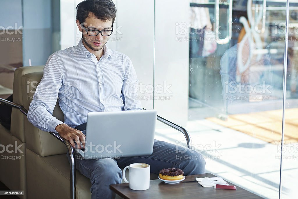 Young businessman with laptop in cafe royalty-free stock photo