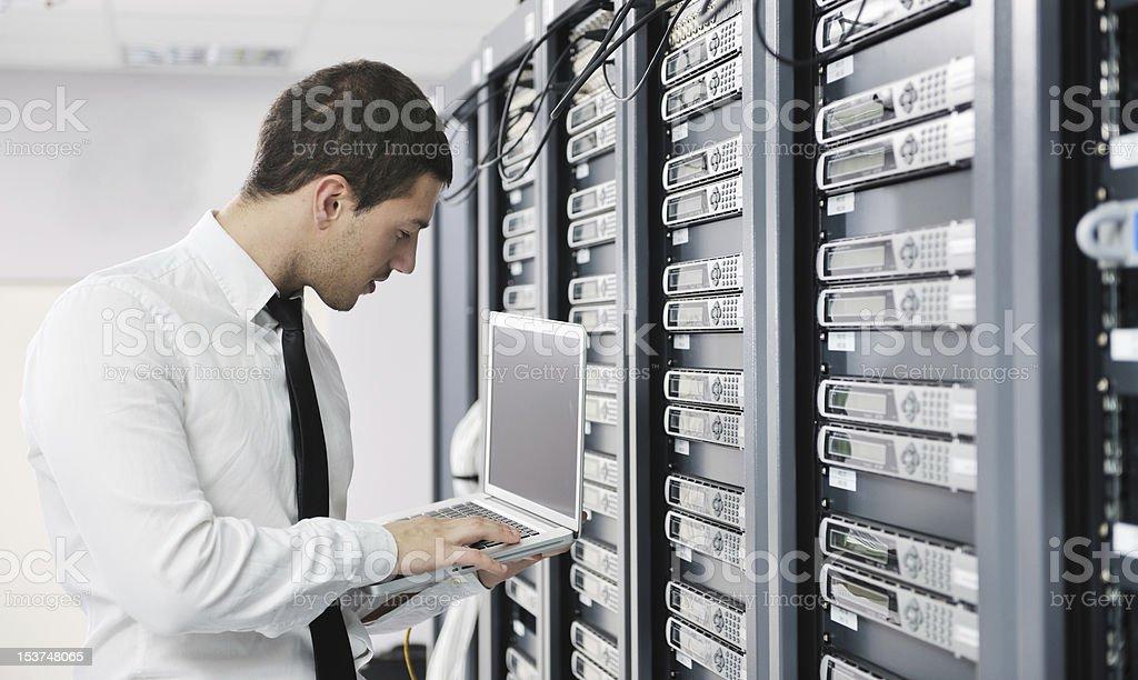 Junger Geschäftsmann mit laptop in server-Raum Lizenzfreies stock-foto