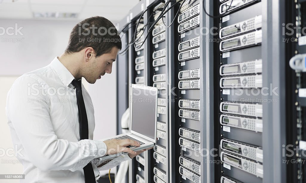 Young businessman with laptop in server room stock photo