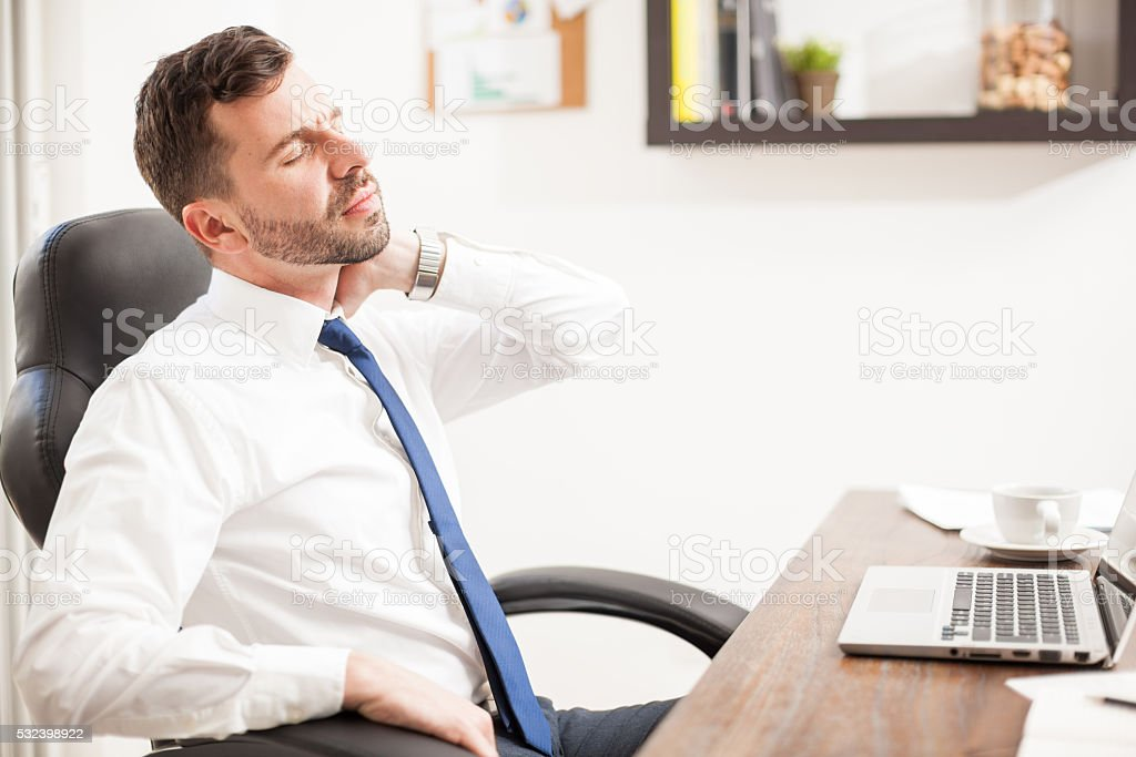 Young businessman with neck pain stock photo