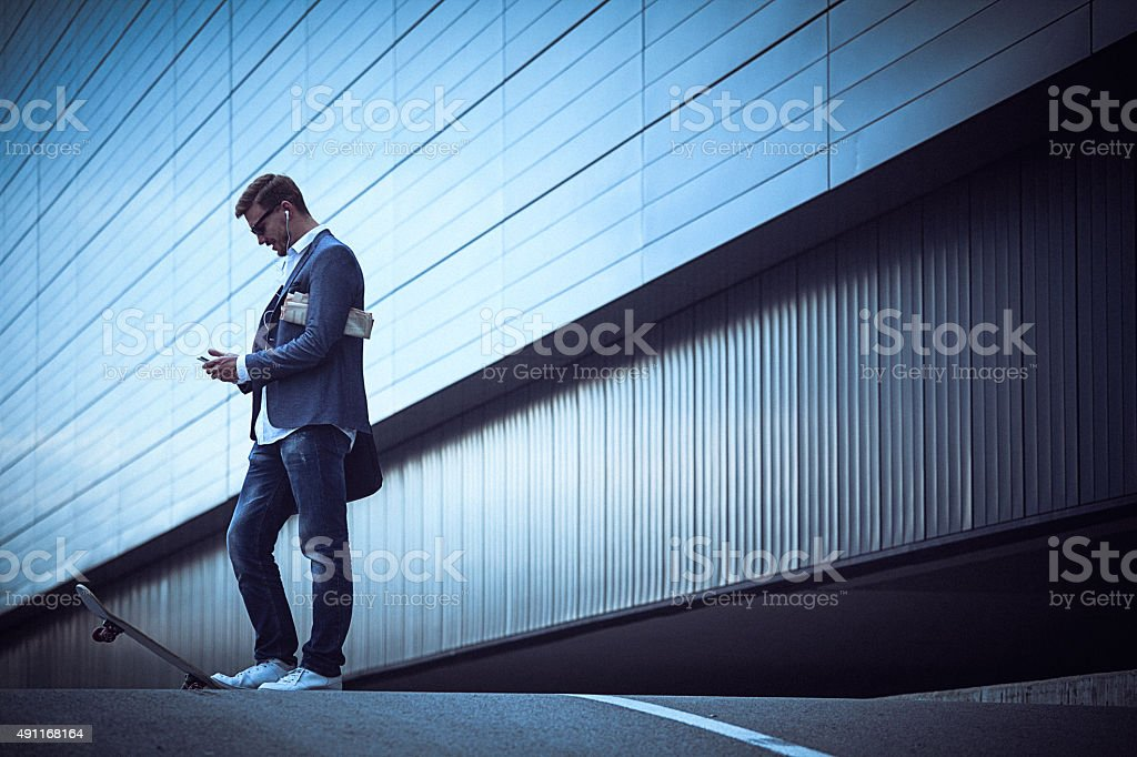 Young businessman with skateboard using smartphone in the urban stock photo