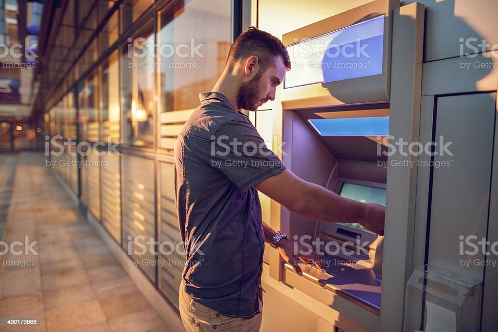 Young businessman withdrawing money from a cash machine. stock photo