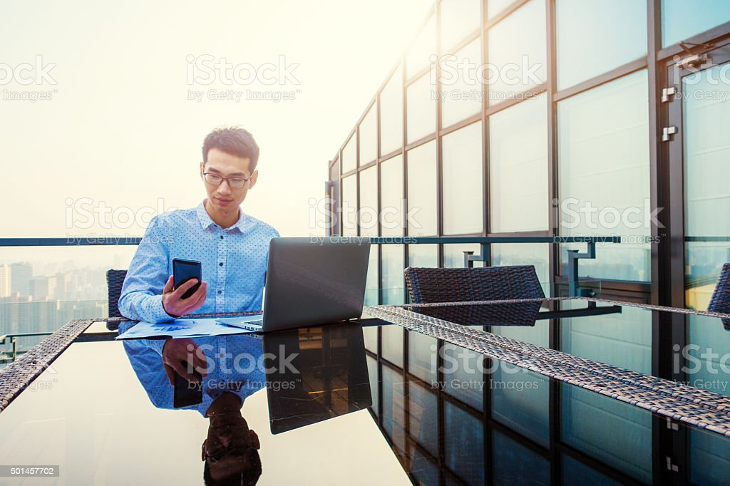 Young businessman working on a laptop and phone stock photo