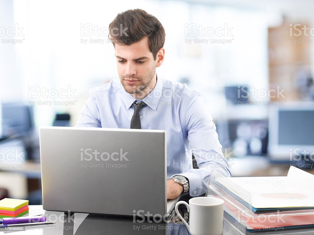 A young businessman working on his laptop with a cup  stock photo