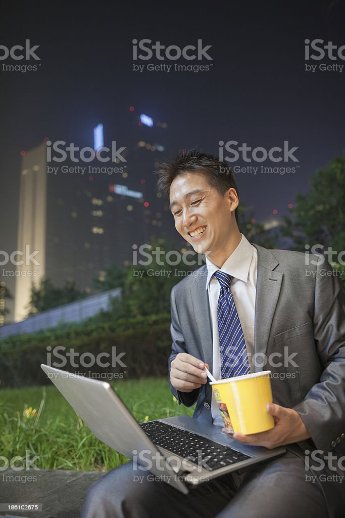 Young businessman working outdoors and eating royalty-free stock photo