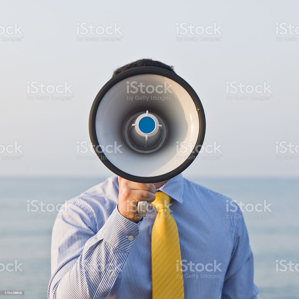 Young businessman  yelling trough a megaphone stock photo