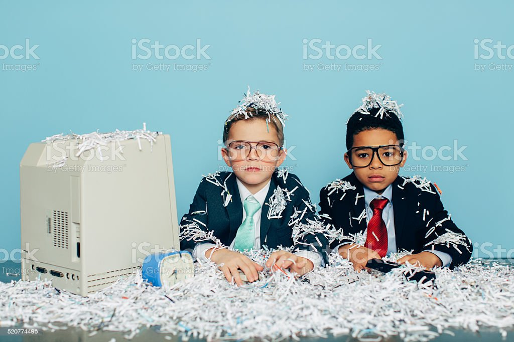 Young Businessmen Covered in Shredded Paper at Office Desk stock photo