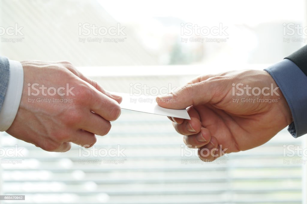 Young businesspeople exchanging Visiting Card In Office stock photo