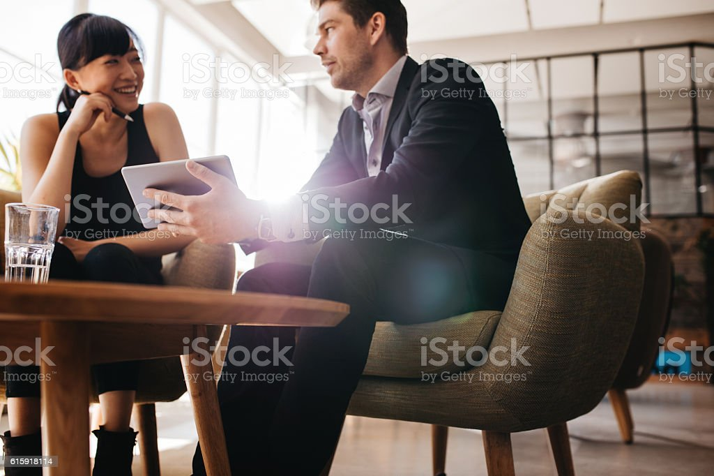 Young businesspeople using digital tablet in lobby stock photo