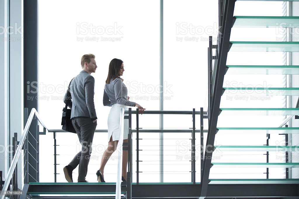Young businesspeople walking on staircase in hallway. stock photo