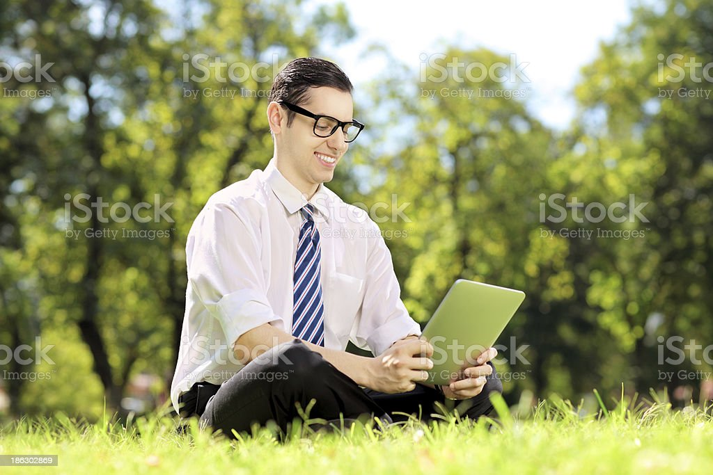 Young businessperson with glasses working on a tablet in park royalty-free stock photo