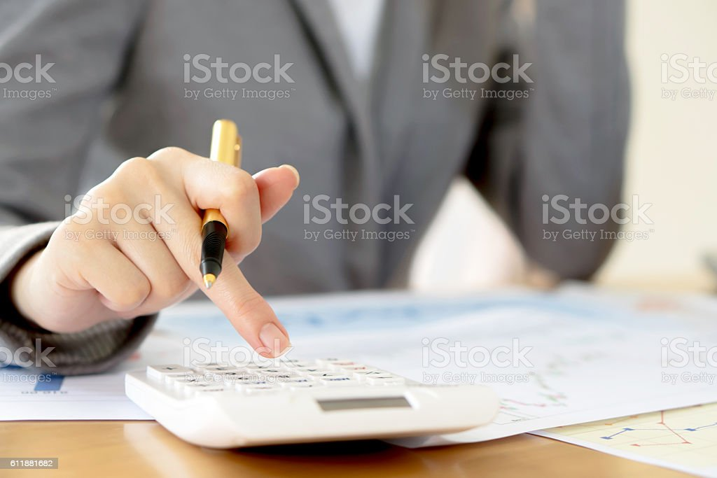 Young Businesswoman Analyzing Report On Chart With Calculator stock photo