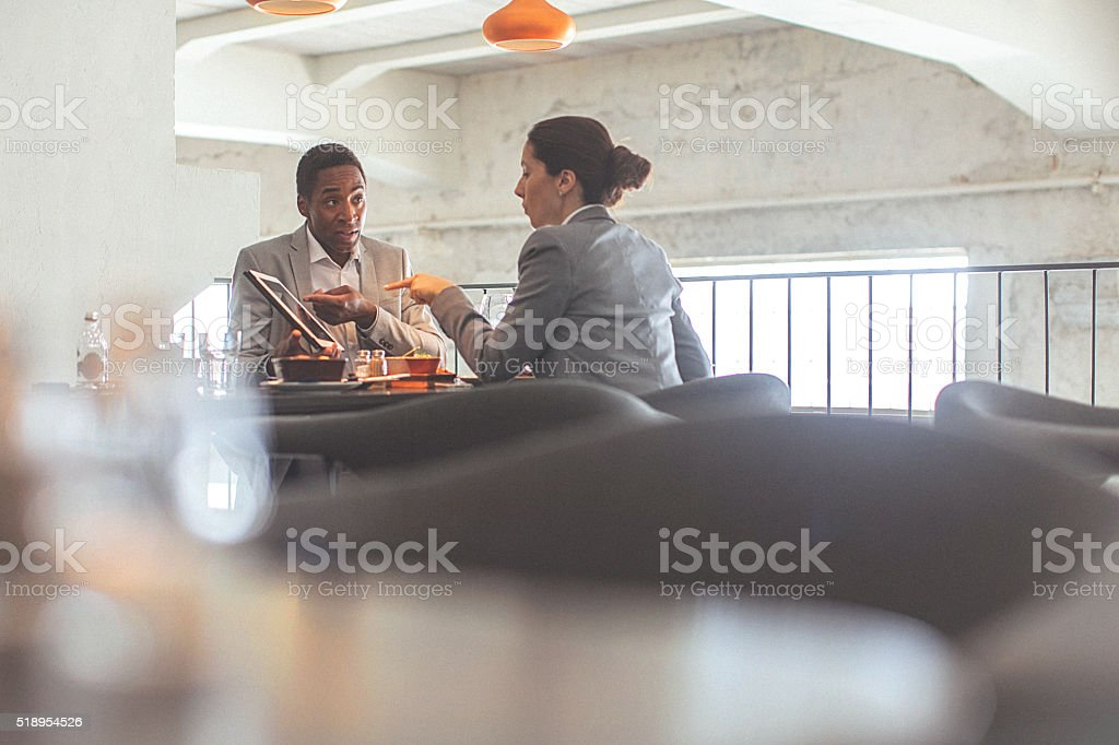Young businesswoman and man having a business conversation at restaurant stock photo