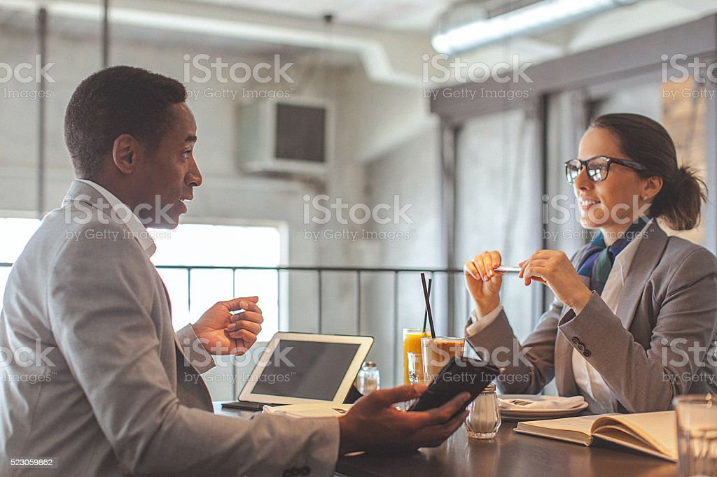 Young businesswoman and man having a conversation in restaurant stock photo