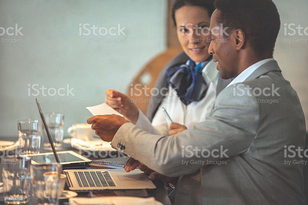 Young businesswoman and man working on a laptop at cafe stock photo