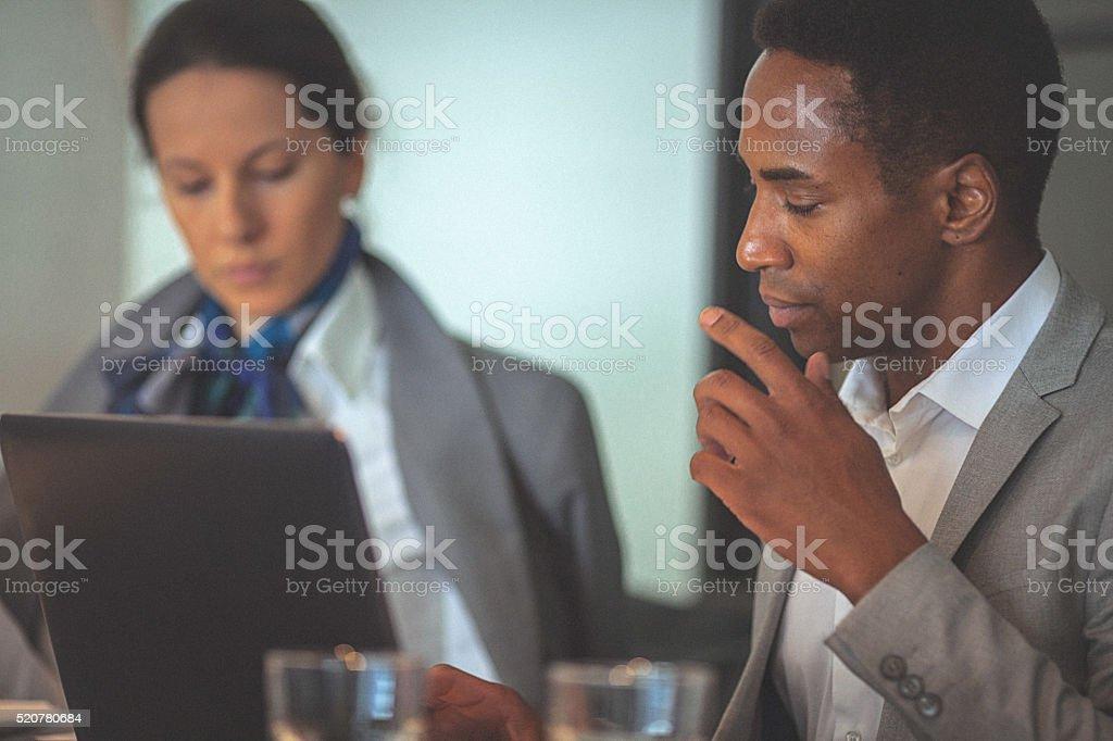 Young businesswoman and man working together on a laptop stock photo