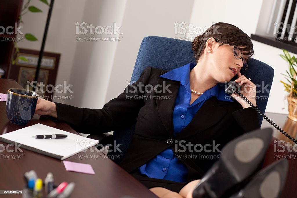 Young Businesswoman Asleep on Phone with Feet on Desk stock photo