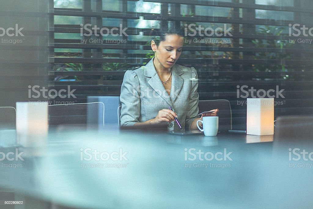 Young businesswoman at cafe using credit card for online transaction stock photo