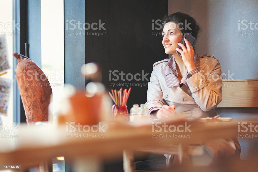Young businesswoman at coffee shop talking on smart phone stock photo