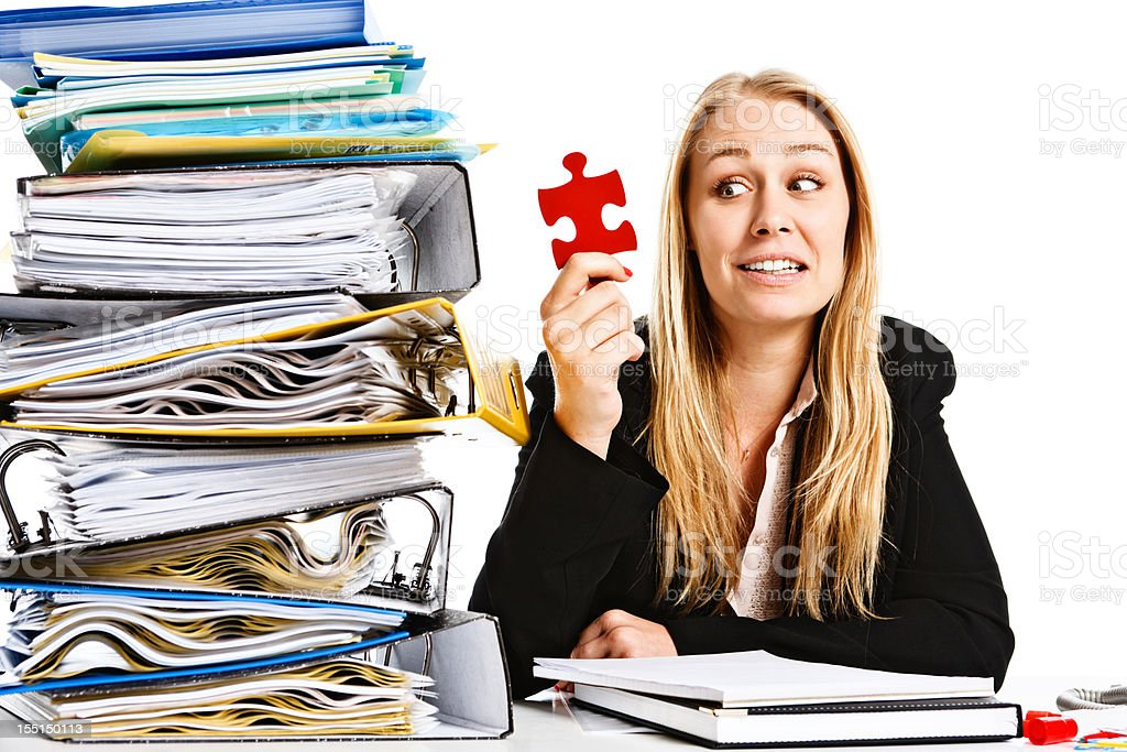 Young businesswoman at crowded desk holds puzzle piece and smiles royalty-free stock photo