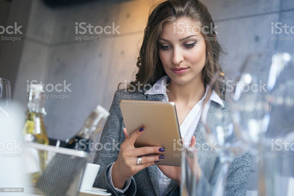 Young businesswoman at restaurant using tablet pc stock photo