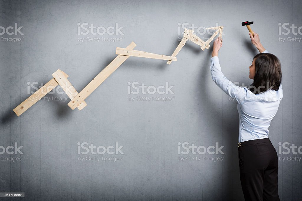 Young businesswoman building pointing up chart. stock photo