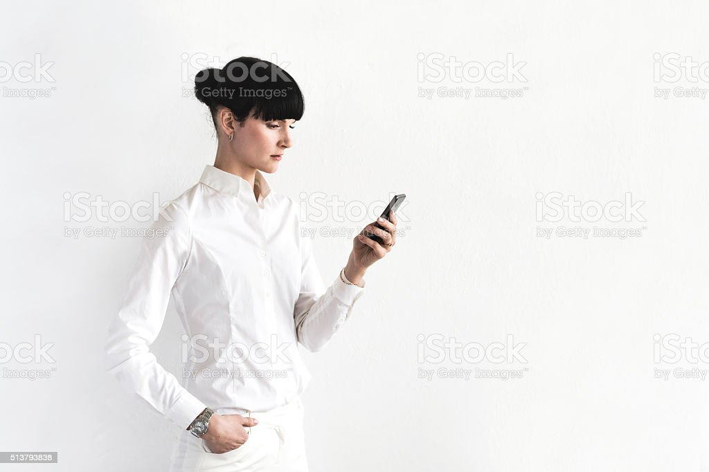 Young Businesswoman Checking Messages on Smartphone in Office stock photo