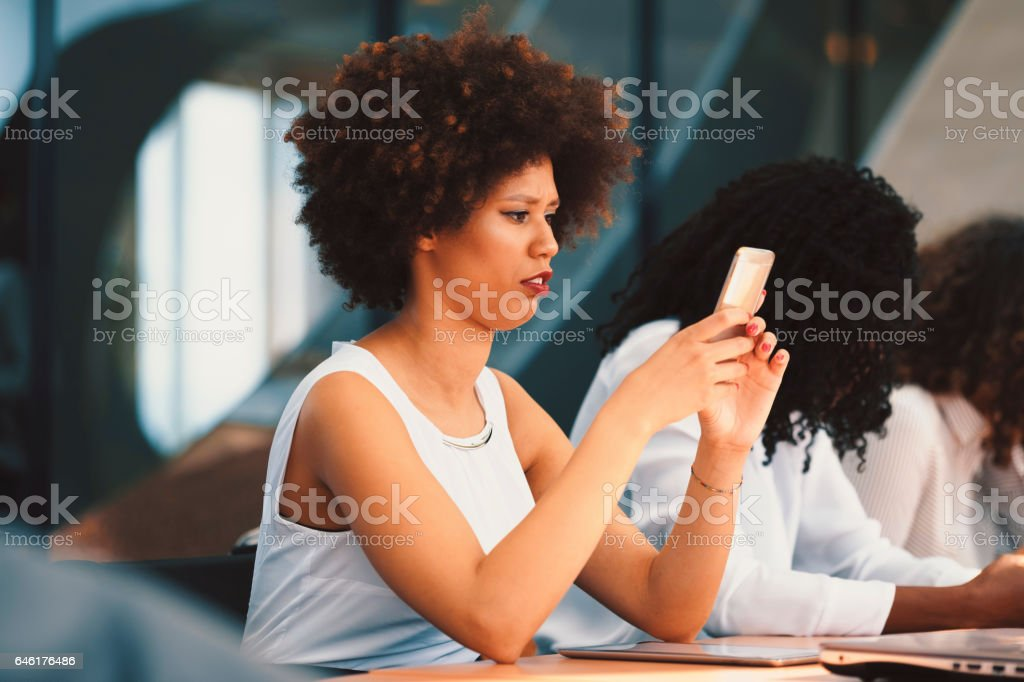 Young businesswoman checking mobile phone stock photo