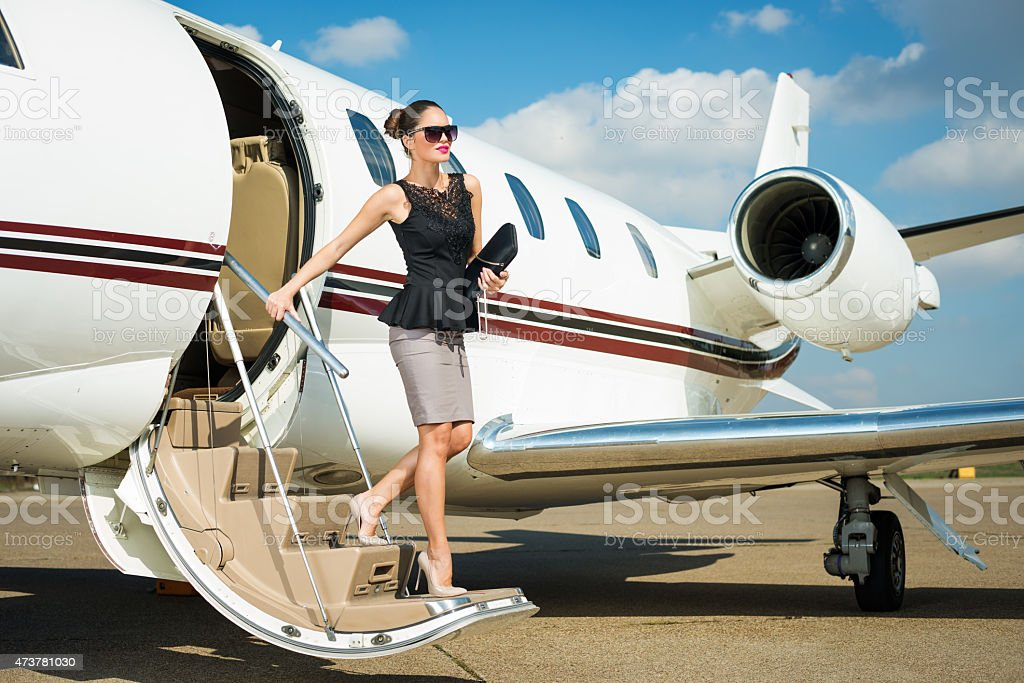 Young businesswoman exiting private jet airplane stock photo