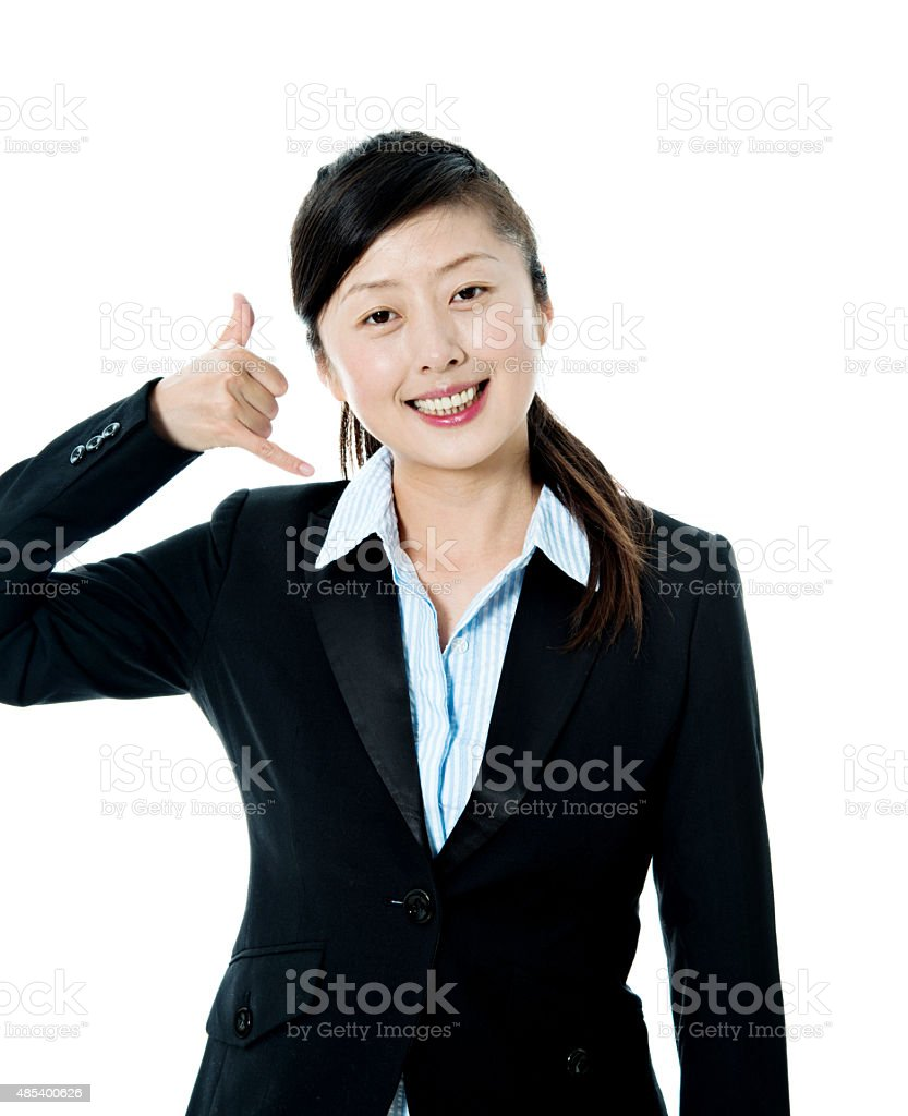 Young businesswoman gesturing call sign stock photo