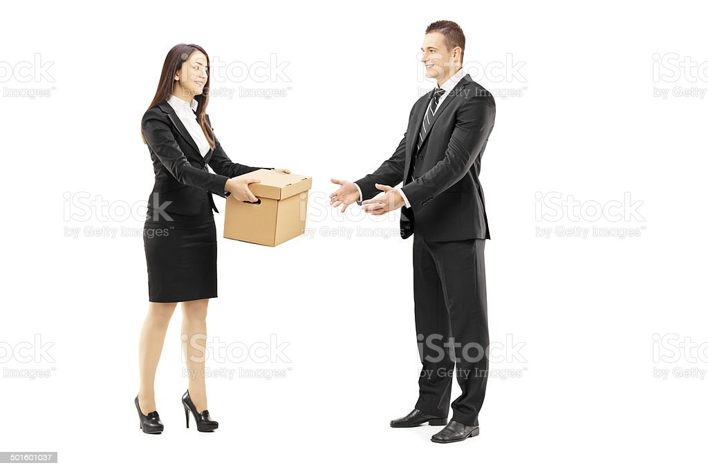 Young businesswoman giving a box to her male colleague stock photo