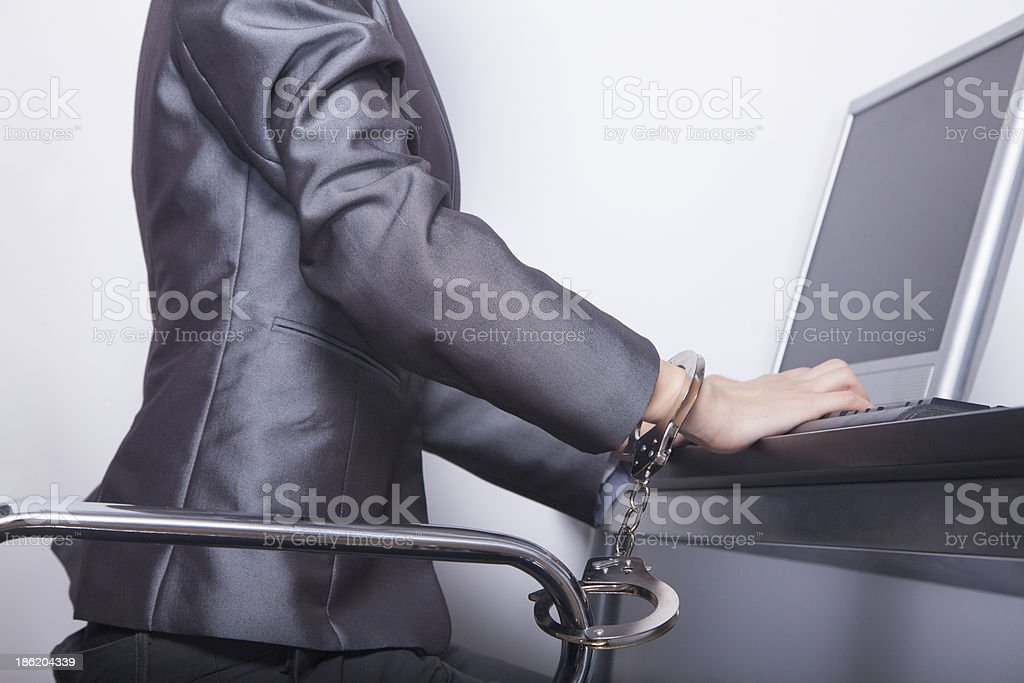 Young businesswoman handcuffed to her office chair royalty-free stock photo