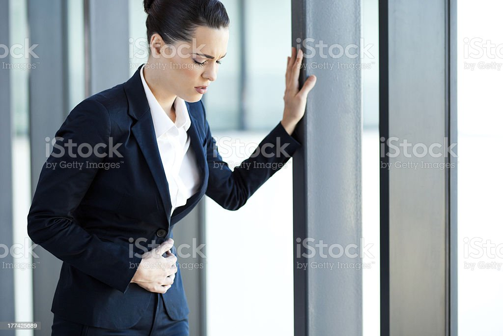 young businesswoman having stomach ache stock photo