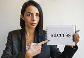 Young businesswoman holding a cardboard sign, success