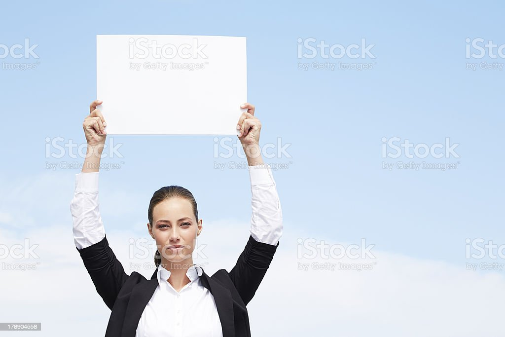 Young businesswoman holding blank sign against blue sky royalty-free stock photo