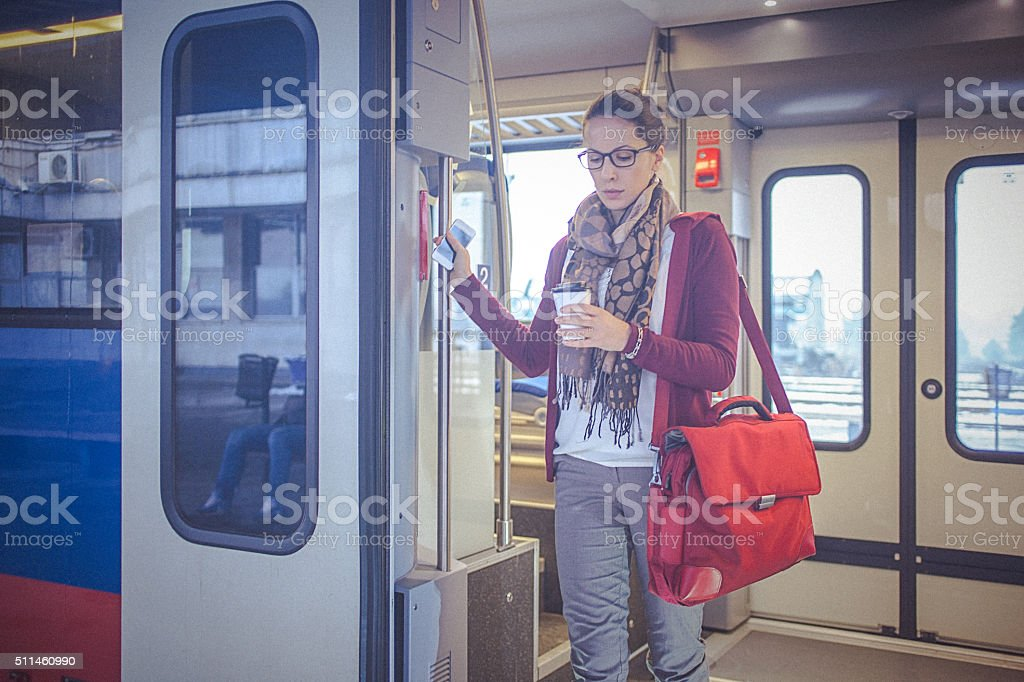 Young businesswoman holding coffee, leaving the train stock photo