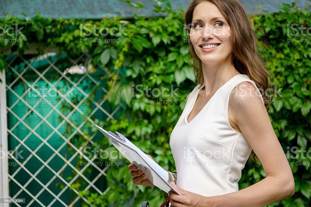 Young businesswoman holding documents outdoors stock photo