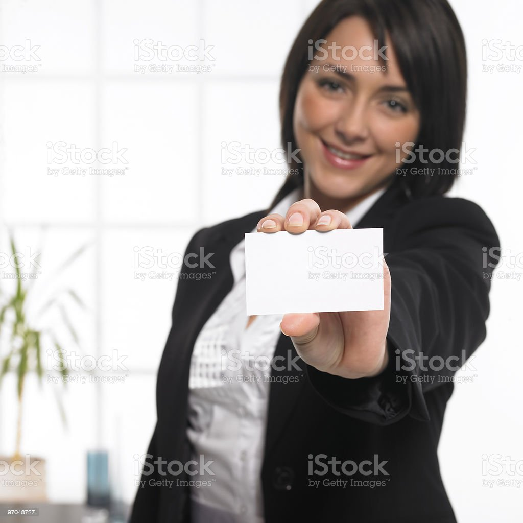 young businesswoman holding empty business card in modern office royalty-free stock photo