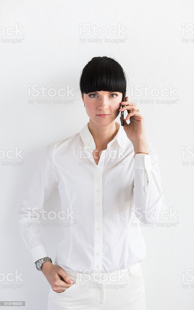 Young Businesswoman Holding Smartphone In Front Of Her stock photo