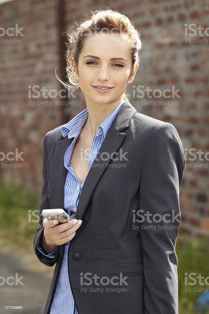 young businesswoman holds her mobile, outdoor shoot royalty-free stock photo